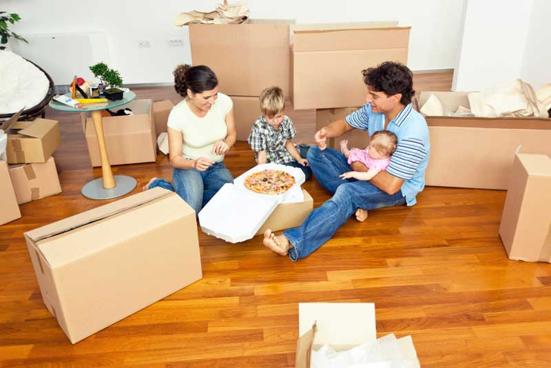 Eltern und zwei Kinder essen Pizza zwischen Umzugskartons
